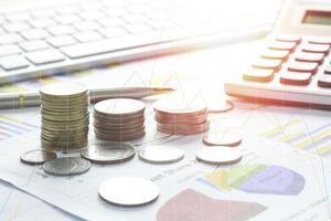 monete su una scrivania con grafici e calcolatrice foto