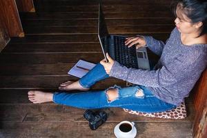 donna che lavora su un computer portatile sul pavimento foto