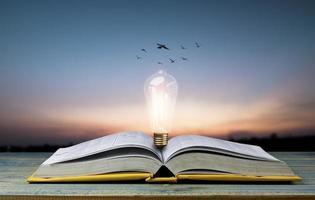 libro aperto con lampadina sul tavolo foto
