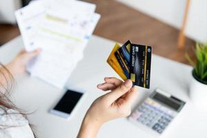 mano della donna che tiene tre carte di credito foto