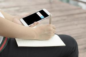 persona che scrive su un blocco note mentre guarda il telefono foto