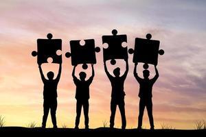 quattro persone in possesso di pezzi di un puzzle silhouette foto