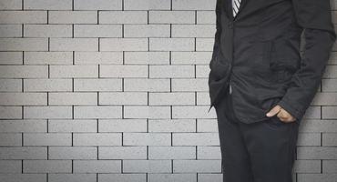 uomo d'affari in piedi sulla priorità bassa del muro di mattoni con lo spazio della copia foto