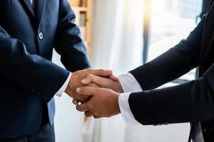 negoziare con successo e concetto di stretta di mano, due uomini d'affari si stringono la mano con il partner per celebrare la partnership e il lavoro di squadra, affare foto