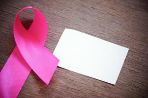 cancro al seno nastro rosa con carta bianca vuota su fondo di legno foto