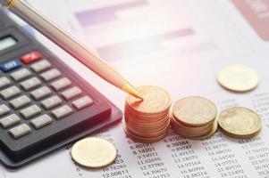 soldi della moneta accatastati con la calcolatrice foto