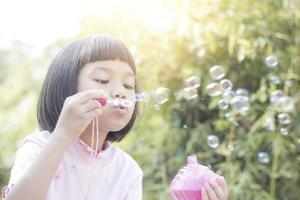 ragazzo asiatico che soffia bolle nel parco foto