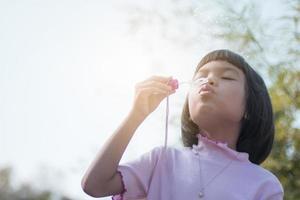 carino ragazzo asiatico che soffia bolle nel parco foto