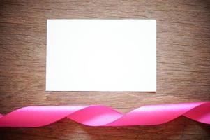 nastro rosa con carta bianca vuota su legno foto