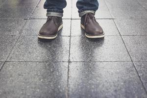un uomo che indossa blue jeans e stivali di pelle foto