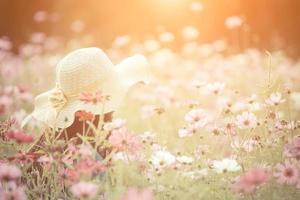 donna che indossa un cappello rosso in un campo di fiori