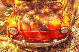 vecchia macchina arrugginita davanti a un muro sporco foto