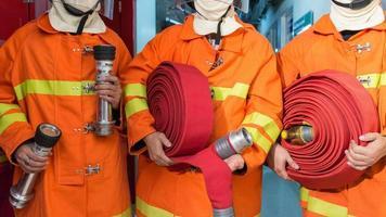 vigili del fuoco in uniforme che tiene attrezzature foto