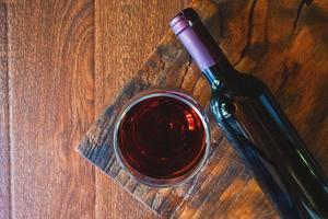 bicchiere di vino e bottiglia di vino sul tavolo di legno foto