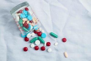 pillole che fuoriescono da una tazza