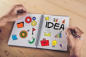 primo piano delle mani che scrivono su carta con l'icona di doodle colorato di affari foto