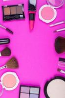 vista dall'alto di una collezione di prodotti cosmetici di bellezza su uno sfondo rosa