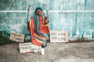 l'uomo si siede accanto alla strada con un messaggio di senzatetto