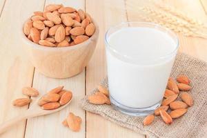 latte di mandorle con mandorle sul tavolo di legno foto