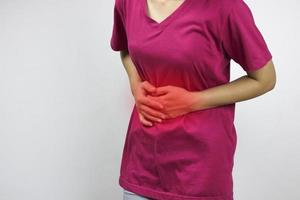 donna in camicia rosa ha mal di pancia foto