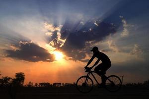 sagoma di un uomo in sella a una bicicletta nel tramonto foto