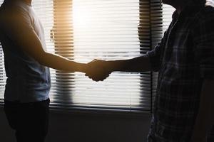 due persone si stringono la mano foto