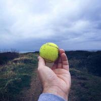 mano con una pallina da tennis foto