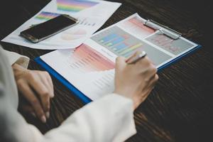 imprenditrice lavorando con analisi documento di marketing foto