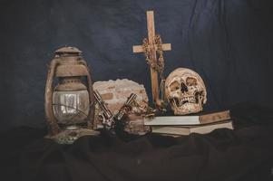 natura morta con teschi sui libri, vecchie lampade, fiori secchi e pistole incrociate foto