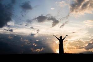 silhouette di donna in piedi con il tramonto foto