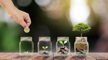 piantare alberi in bottiglie trasparenti per risparmiare denaro su un tavolo di legno e idee di crescita aziendale sfondo verde sfocato foto