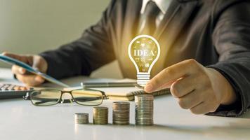 uomo d'affari che tiene una lampadina, idee sulla sua scrivania, idee per la finanza, gli investimenti e la gestione di un'impresa di successo foto