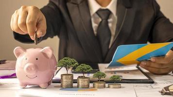 piantare un albero su un mucchio di soldi e uomo d'affari, uomo che risparmia denaro, idee per risparmiare denaro per investimenti futuri foto