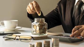 primo piano di persone che mettono monete in bottiglie per il risparmio di denaro e calcolatrici in idee per il risparmio di denaro e bancarie foto