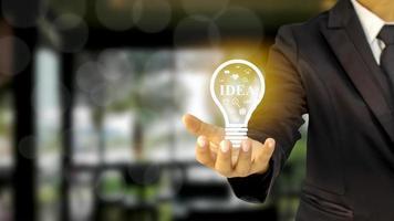 uomo d'affari in possesso di una lampadina idea di idee finanziarie, investire e gestire un business di successo foto