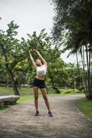 giovane donna sportiva che si estende nel parco foto