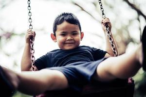 adorabile ragazzino divertendosi su un'altalena all'aperto foto