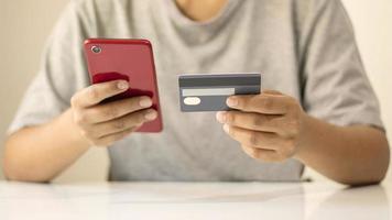 uomo asiatico che paga con carta di credito online mentre ordina su Internet a casa, idea di transazione utilizzando l'applicazione di mobile banking