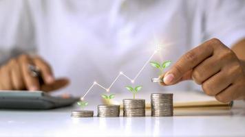 concetto di crescita degli investimenti aziendali, un mucchio di monete con un piccolo albero che cresce su una moneta e una mano che tiene una moneta foto