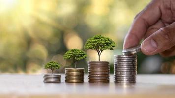 concetto di crescita finanziaria da investimenti aziendali, mucchio di monete con un piccolo albero che cresce su una moneta e moneta che tiene la mano foto
