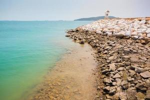 oceano blu brillante con una spiaggia rocciosa foto