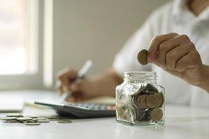 primo piano di una giovane donna che mette una moneta in una bottiglia, risparmiando denaro, un concetto di risparmio di denaro per la contabilità finanziaria foto