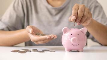 le donne mettono monete d'argento nei suinetti per risparmiare denaro e risparmiare denaro per investimenti futuri. concetto finanziario foto
