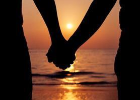 silhouette di una coppia mano nella mano al tramonto foto