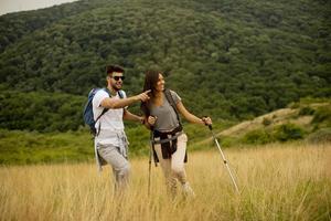 coppia sorridente che cammina con zaini su verdi colline foto