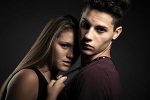 ritratto di una giovane bella coppia felice contro uno sfondo grigio scuro foto