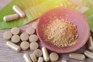 polvere di erbe e medicina in una ciotola di legno foto