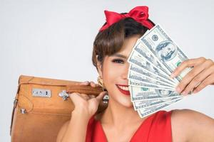 donna alla moda retrò tiene bagagli e soldi per viaggiare foto