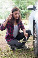 donna giovane hipster controllando una gomma a terra sulla sua auto