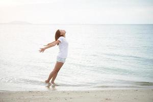 giovane bella donna in piedi che allunga le braccia in spiaggia foto